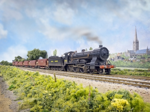 "A Drummond T14 4-6-0 ""Paddlebox"" 461 a NuCast kit heads towards London with a Meldon Quarry Ballast train. The SR Diagram 1774 40T hoppers are modified LIMA wagons on new bogies and other details. Salisbury Cathedral can be seen in the background"