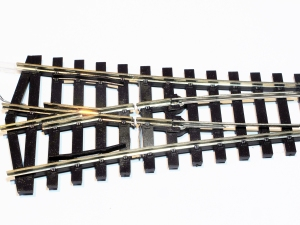 The Peco short radius 'Y' turnout does not have wire links so requires the actual rails to be cut between the frog and links between the stock rails and the switch blade (just visible)