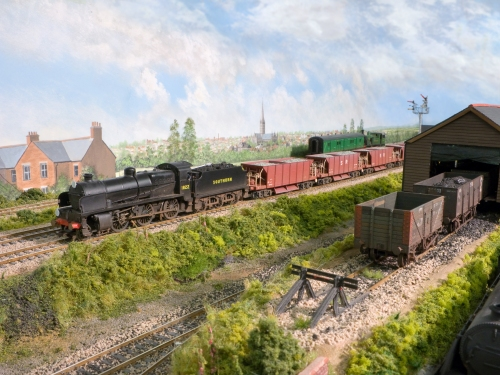A Maunsell N1 class, a modified Bachmann model hauls ballast train past the shed. The SR Diagram 1774 40T hoppers are modified LIMA wagons on new bogies and other details. Salisbury Cathedral can be seen in the background.